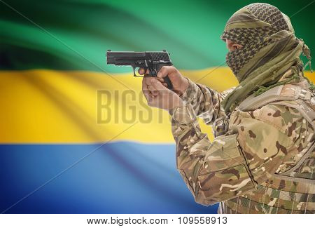 Male In With Gun In Hand And National Flag On Background - Gabon