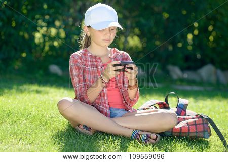 Schoolgirl Sitting On The Grass Playing With His Phone