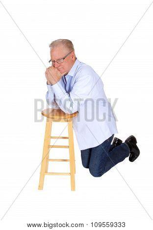 Older Man Kneeling And Praying.