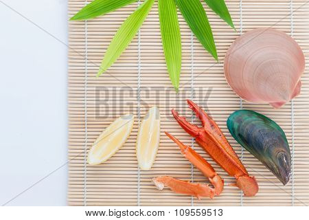 Raw Queen Scallops ,mussel And Crab Claws With Lemon Slice  On Bamboo Background And  Bamboo Leaves