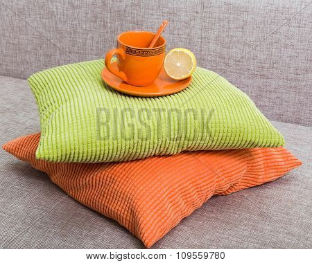 Ceramic Orange Cup With A Lemon Half On A Saucer On A Pile From Green And Orange Pillows On A Gray S