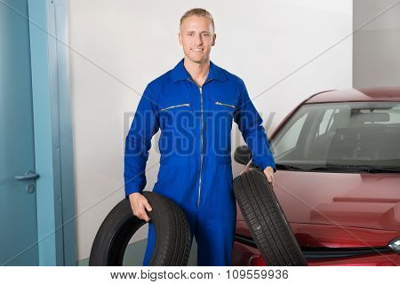 Mechanic Holding Tires