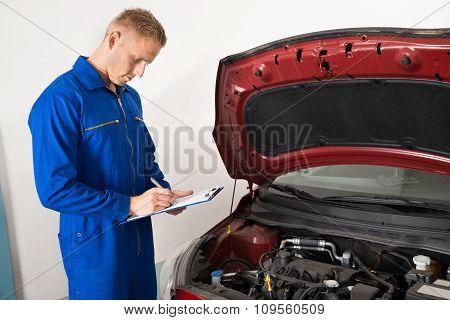 Mechanic Standing Near Car Writing On Clipboard
