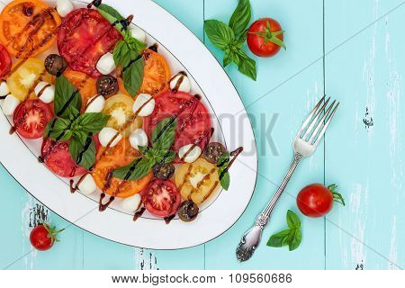 Italian caprese salad with mozarella cheese tomatoes and basil on vintage wooden background. Top vie