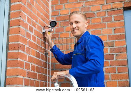 Smiling Technician Installing Camera On Wall