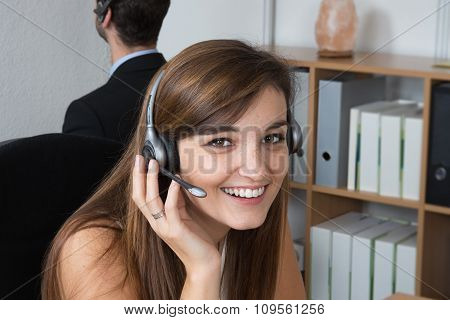 Portrait Of Beautiful Business Woman Working At Her Desk With Headset