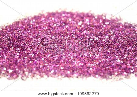 Blurry background of purple glitter sparkles on white surface