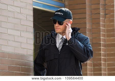 Young Security Guard Standing In Front Of The Entrance