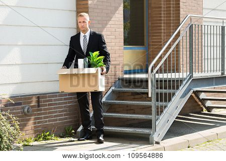 Businessman Standing With Cardboard Box