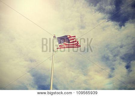 Vintage Toned American Flag Against Sun.