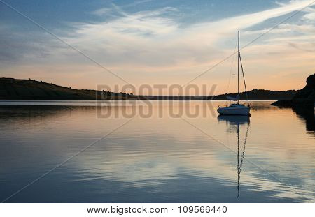 Sunset Over Alange Reservoir With Anchored Sailboat, Spain