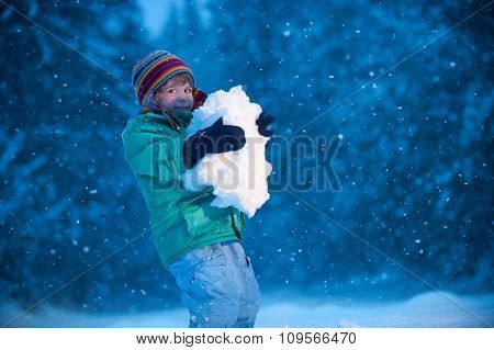 Little boy holding snowball