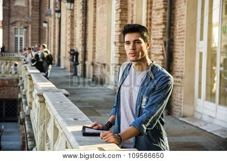 Young Man Holding a Guide Outside Historic Building