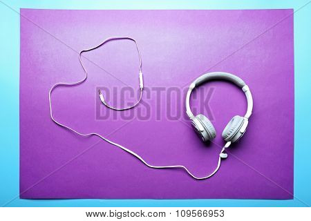 White and grey headphones on purple-blue background