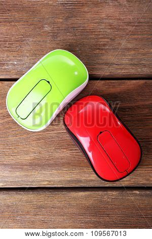 Wireless computer mouses on wooden background