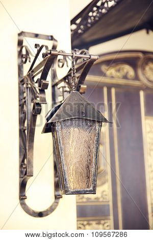 Vintage old bronze lantern on the wall