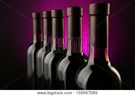 Wine bottles in row on dark purple background
