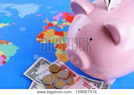 Piggy money box, banknotes and coins on world map background