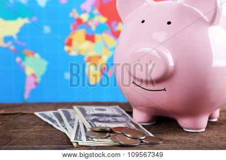 Piggy money box, banknotes and coins on wooden table, close-up