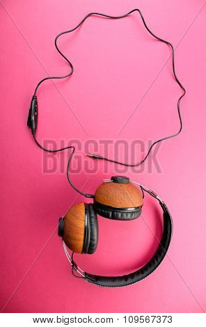 Black and brown headphones on pink background