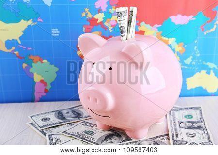 Money box pig on world map background