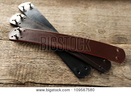 Leather bracelets on wooden background