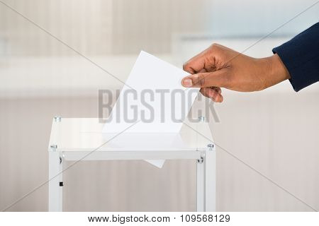 Person's Hand Putting Ballot In Box