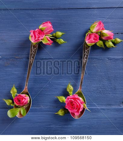 Creative music notes made of flowers and spoon on blue wooden background