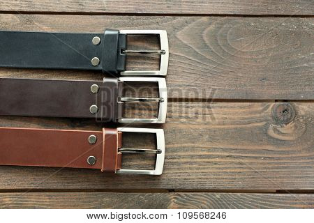 Leather belts with buckles on wooden background