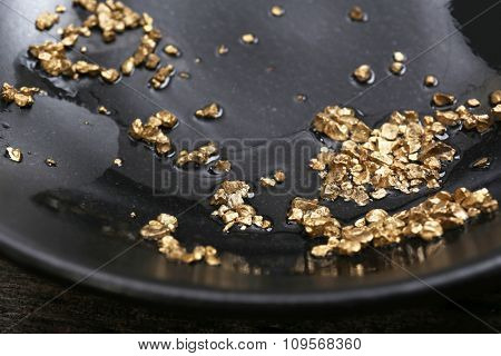 Gold nugget grains, on black plate, close-up
