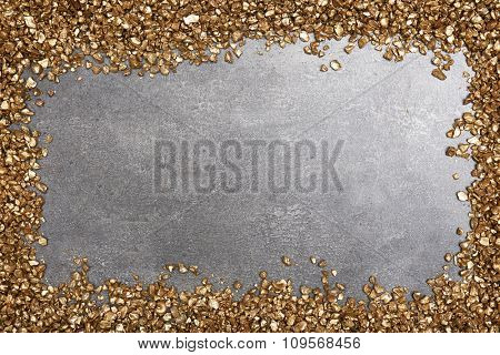 A frame of Gold nugget grains, on cement background