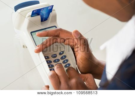 Person's Hand Using Credit Card Machine