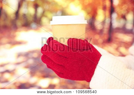 Woman holding cup of hot beverage in park