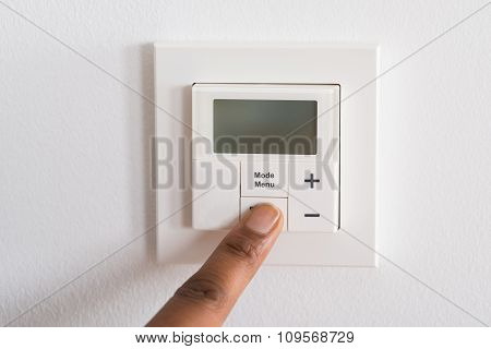 Person's Finger Adjusting Room Temperature On Digital Thermostat