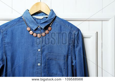 Denim shirt and necklace on hanger on wall background