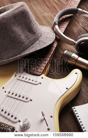 Electric guitar with headphones, hat and microphone on wooden background