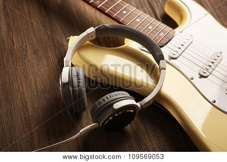 Electric guitar with headphones on wooden background
