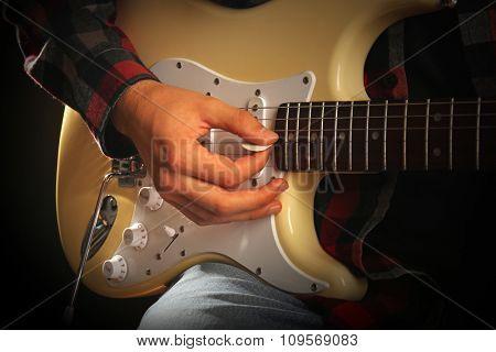 Musician plays electric guitar, close up
