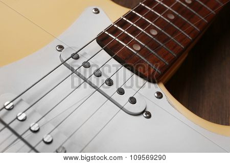 Electric guitar on wooden background, close up