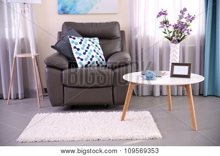 Modern living room interior with coffee table, armchair and stand