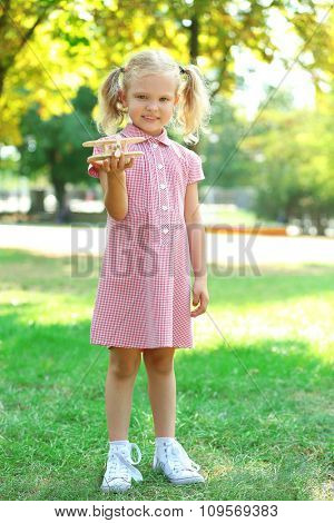 Blonde little girl plays with wooden plane at the park