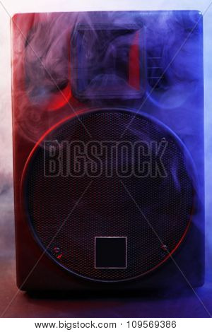 Black loudspeaker in a smoke on dark background