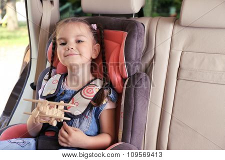 Cute little girl sitting in the car and playing with wooden plane