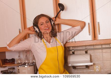 Housewife With Earphones In Kitchen