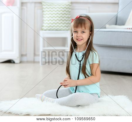 Little cute girl with stethoscope sitting on carpet, on home interior background