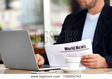 Young attractive businessman having lunch and working in a cafe, close-up