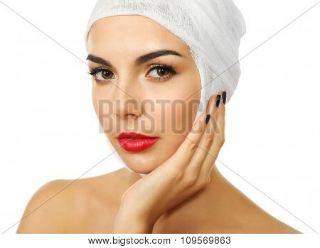 Young beautiful woman with a gauze bandage on her head, isolated on white, close-up