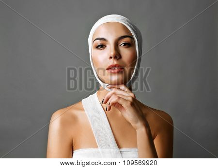 Young emotional woman with  a gauze bandage on her head and chest, on grey-blue background