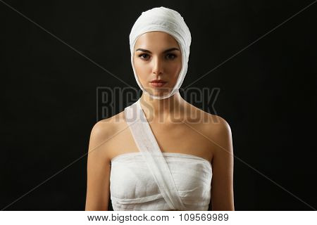 Young beautiful woman with a gauze bandage on her head and chest, on black background