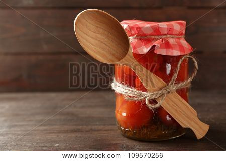 Jar of canned tomatoes on wooden background